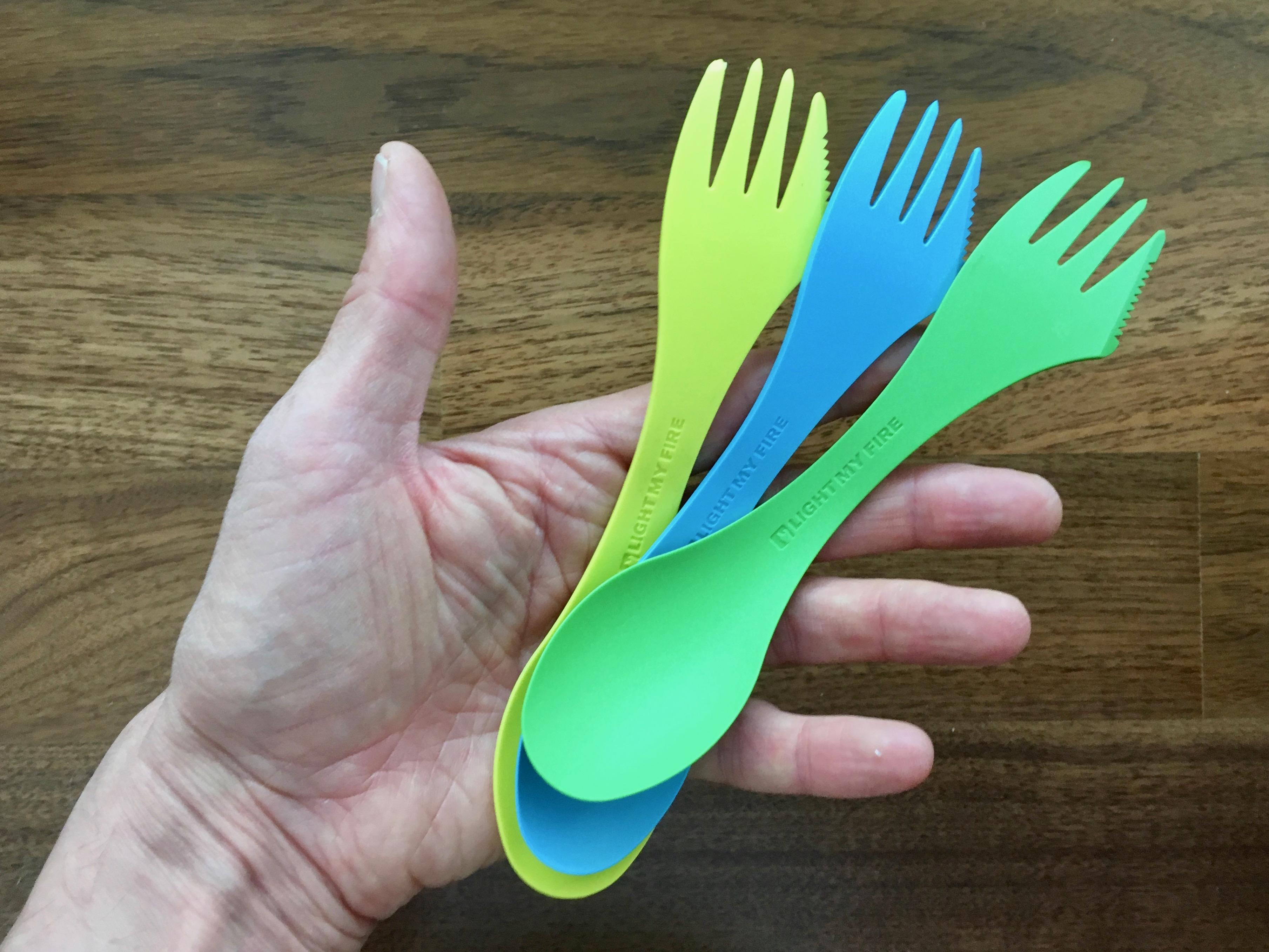 Foto Hand mit Auswahl an farbigen Esslöffeln Didaktische Reduktion